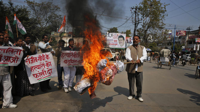 """India's ruling Congress party supporters burn an effigy of Tamil Nadu state chief minister Jayaram Jayalalitha during a protest in Allahabad, India, Thursday, Feb. 20, 2014. The Tamil Nadu state had ruled Wednesday that seven men serving life sentences for the 1991 assassination of former Prime Minister Rajiv Gandhi should be freed because they have served more than 20 years in prison. India's top court on Thursday stopped the government of Tamil Nadu state from releasing three of the seven prisoners, a lawyer said. The banners read: """"Hang Rajiv Gandhi's killers.""""(AP Photo/ Rajesh Kumar Singh)"""