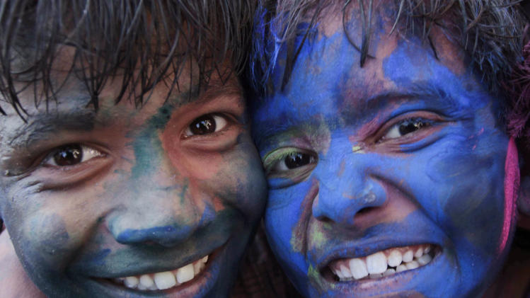 Indian children react to camera as they play with colored powder ahead of the Holi festival in Ahmadabad, India, Saturday, March 15, 2014. Holi, the Hindu festival of colors that also marks the advent of spring, is being celebrated across the country Monday. (AP Photo/Ajit Solanki)