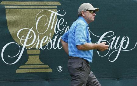 International Team captain Nick Price of Zimbabwe carries a two-way radio during the second practice round for the 2013 Presidents Cup golf tournament at Muirfield Village Golf Club in Dublin, Ohio