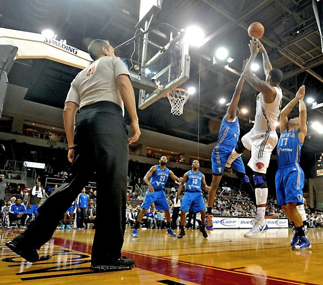 Texas Legends' Melvin Ely, middle left, is kicked while Erie Bayhawks' Jeremy Tyler, middle, shoots a jump shot during the second quarter of an NBA D-League basketball game in Erie, Penn., on