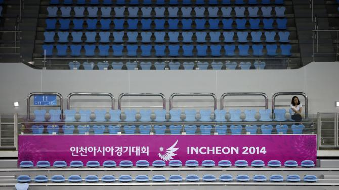 A woman sits on a bleacher at the Gyeyang Gymnasium in Incheon