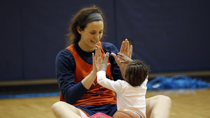 "In this Jan. 27, 2015, photo, University of Virginia basketball player Sarah Beth Barnette plays with Ngoty, the adopted daughter of Virginia women's basketball coach Joanne Boyle in Charlottesville, Va. When the team travels, Ngoty often goes along, riding with the players and her mom. On one recent two-hour bus trip home from Virginia Tech, Ngoty sat on Boyle's lap, watching ""The Jungle Book"" on an iPad as Boyle watched game film on her laptop.  (AP Photo/Alex Brandon)"