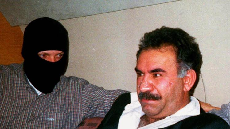 "FILE - In this  Monday Feb. 15, 1999 file photo  provided by the Turkish Intelligence Service o the chief of the Kurdistan Workers Party, PKK, Abdullah Ocalan sits guarded aboard an aircraft en route to Turkey following his arrest by Turkish special forces in Nairobi, Kenya. Imprisoned Kurdish rebel leader Abdullah Ocalan said Monday, March 18, 2013 that peace talks with Turkey are making ""positive progress"" and that he plans to make a ""historic"" announcement to coincide with a Kurdish spring festival. (AP Photo/Turkish Intelligence Service, File)"