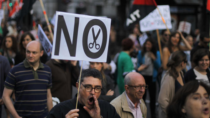 """Protestors hold a banner reading """"no cuts"""" as they march against healthcare austerity measures announced by the Spanish government in defense of the public healthcare system in Madrid, Spain, Saturday, Oct. 6, 2012. Hundreds of Spaniards concerned with government cuts to healthcare and civil servants hit with another freeze on their wages for next year hold a protest in downtown Madrid. (AP Photo/Andres Kudacki)"""