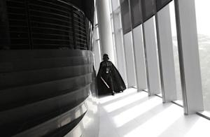 """An entertainer dressed as Darth Vader from """"Star Wars"""" walks down the corridor to pose for the media during the opening of Lucasfilm's new animation production facility, the Sandcrawler, in Singapore"""
