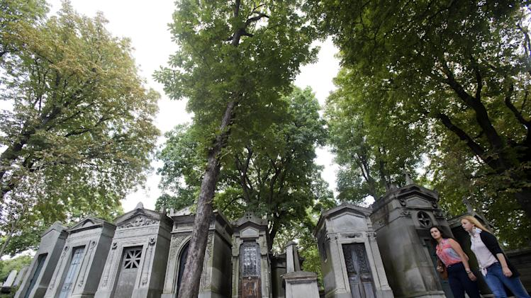 FILE--In an Aug. 30, 2012 file photo people walk past chestnut trees and graves at Pere Lachaise cemetery in Paris.  It seems that a moth has bought the noble tree low, according to Dr. Darren Evans of the University of Hull in England, without a cure in sight. (AP Photo/Michel Euler, file)