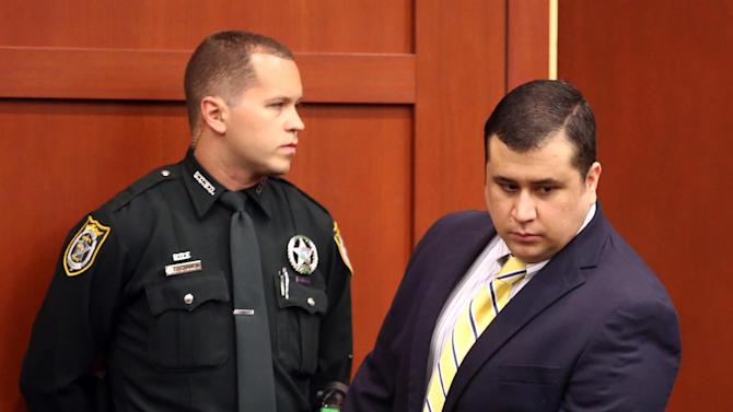 """George Zimmerman, defendant in the killing of Trayvon Martin, walks by an officer in Seminole circuit court, in Sanford, Fla., during a pre-trial hearing, Tuesday, April 30, 2013.   Zimmerman says he agrees with his attorneys' decision not to seek an immunity hearing under the state's """"Stand Your Ground"""" self-defense law. (AP Photo/Orlando Sentinel, Joe Burbank, Pool)"""