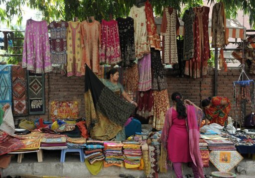 <p>An Indian woman arranges goods for sale at a market in New Delhi April 2012. India's once-booming economy is suffering from slowing industrial growth, troublesome fiscal and current account deficits, stubbornly high inflation and a stalled reform agenda.</p>