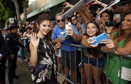 "Gomez waves while greeting fans at the premiere of ""Getaway"" in Los Angeles"