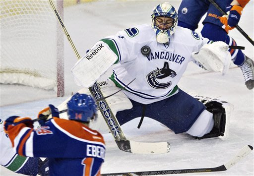 Vancouver Canucks' Roberto Luongo makes the save on Edmonton Oilers' Jordan Eberle, left, during the third period of an NHL hockey game in Edmonton, Alberta, Monday, Feb. 4, 2013. Vancouver won 3-2. (AP Photo/The Canadian Press, Jason Franson)