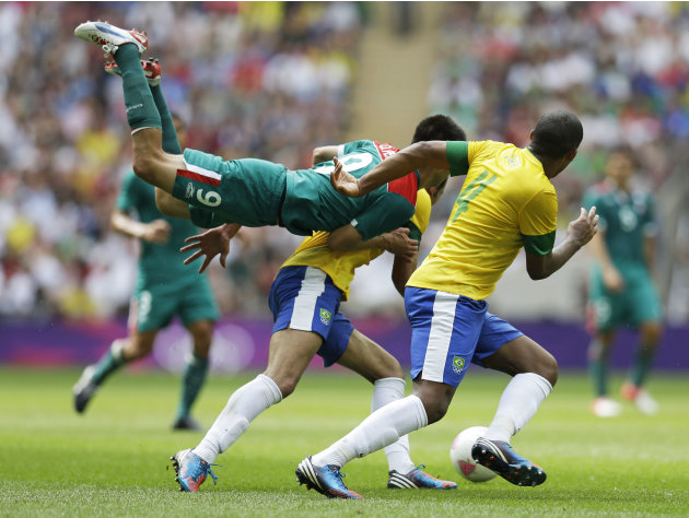 Mexico's Oribe Peralta, middle, goes airborne in front of Brazil's Juan Jesus, right, as they pursue the ball during the men's soccer final at the 2012 Summer Olympics, Saturday, Aug. 11, 2012, in Lon