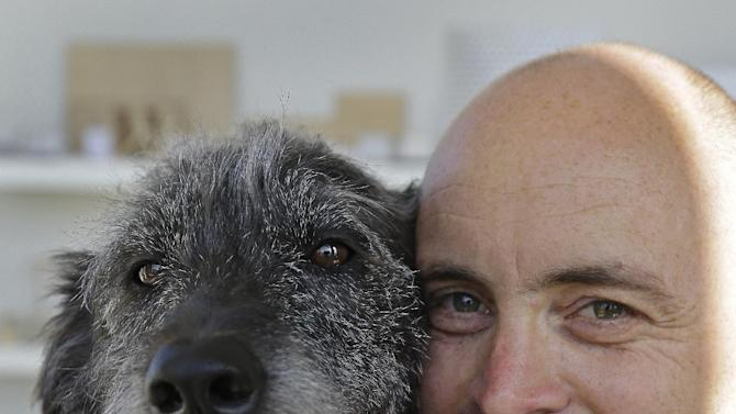 Martin Sprouse with 'Grady', an Airedale Terrier-Irish Wolfhound mix, Thursday, April 18, 2013, in Oakland, Calif. After his owner brought the dog to the Kauai Humane Society because he was moving, the dog with the big brown eyes languished for four months, said shelter operations manager Brandy Varvel. But now Grady is living in a spacious California loft with a new owner who is admittedly smitten thanks to an arrangement the Kauai Humane Society has with the East Bay SPCA in Oakland.  (AP Photo/Ben Margot)