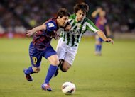 Barcelona's Lionel Messi (L) clashes with Real Betis' Benat Etxebarria during their Spanish La Liga match at Benito Villamarin stadium in Sevilla. The match ended in a 2-2 draw
