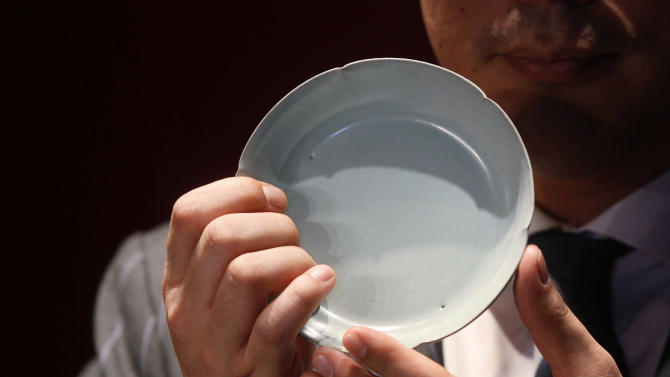 Nicolas Chow, Sotheby's Asia Deputy Chairman, holds the Chinese Song Dynasty ceramics Ruyao Washer at the Sotheby's auction in Hong Kong Wednesday, April 4, 2012. The 900-year-old dish smashed the world record for Chinese Song Dynasty ceramics sold at auction, fetching US$26.7 million. (AP Photo/Kin Cheung)