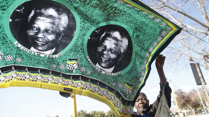 "A souvenir vendor set up his street shop with scarves showing portraits of former South African President Nelson Mandela near the Hector Peterson Museum in Soweto, Saturday June 29, 2013. The White House issued a statement Saturday that President Barack Obama plans to visit privately with relatives of former South African President Nelson Mandela, but doesn't intend to see the critically ill anti-apartheid activist he has called a ""personal hero."" (AP Photo/Markus Schreiber)"