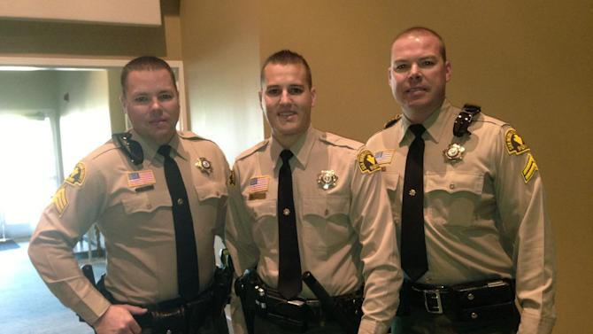 In this May 14, 2013 photo provided courtesy of Lila Collins shows San Bernandino County Sheriff's Department deputies and brothers, Sgt. Ryan Collins, 39, left, Det. Alex Collins, 27, center and and SWAT Det. Matt Collins, 37. (AP Photo/Lila Collins)