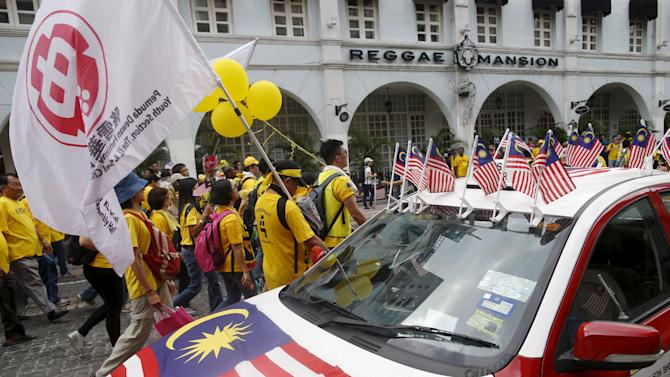 "Supporters of pro-democracy group ""Bersih"" (Clean) pass a taxi decorated with Malaysian flags as they march towards Dataran Merdeka in Malaysia's capital city of Kuala Lumpur"