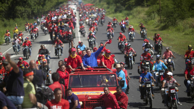 Venezuela's President Hugo Chavez waves to supporters from the top of a vehicle driven by Venezuela's Foreign Minister Nicolas Maduro during a campaign caravan from Barinas to Caracas, in Sabaneta, Venezuela, Monday, Oct. 1, 2012. Venezuela's presidential election is scheduled for Oct. 7. (AP Photo/Rodrigo Abd)