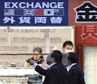 <p>Pedestrians walk past a foreign currency exchange in Tokyo. The Bank of Japan on Thursday said it expected the world's third-largest economy to expand by 2.2 percent in the fiscal year through March 2013 as it held off ushering in fresh stimulus.</p>