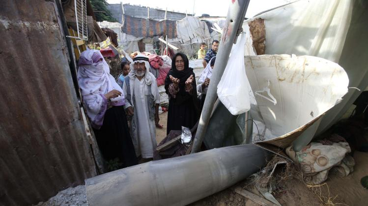 A Palestinian woman gestures as she stands behind a missile which witnesses said was fired by Israeli aircraft, at a shack belonging to Bedouins in Rafah, in the southern Gaza Strip