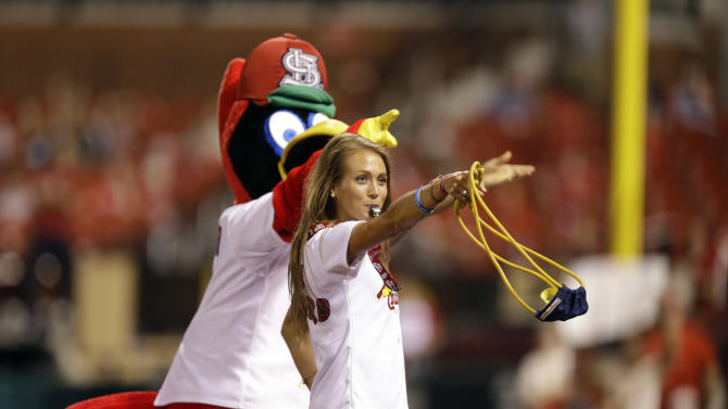 A St. Louis Cardinals cheerleader gives away t-shirts along side team mascot Fredbird between innings of a baseball game early between the St. Louis Cardinals and the Chicago White Sox Thursday, July 2, 2015, in St. Louis. (AP Photo/Jeff Roberson)