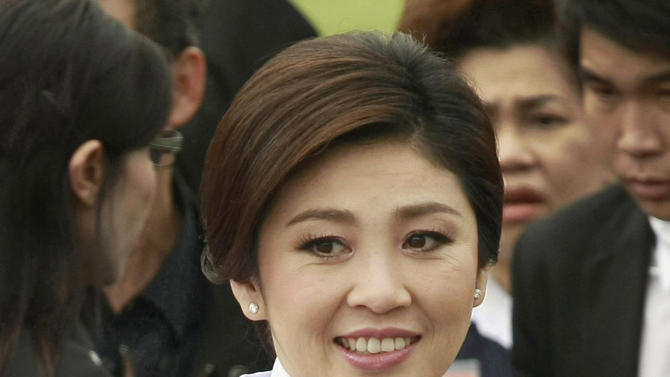 In this photo taken Aug. 10, 2011, Thai Prime Minister Yingluck Shinawatra smiles after a group photo with her cabinet members following an oath taking ceremony at the government house in Bangkok, Thailand. As she marks a year in office as Thailand's first female prime minister, Yingluck's biggest boast could be about what she hasn't brought to Thai politics, a return to the chaos that has wracked the country for much of the past six years. (AP PhotoApichart Weerawong)