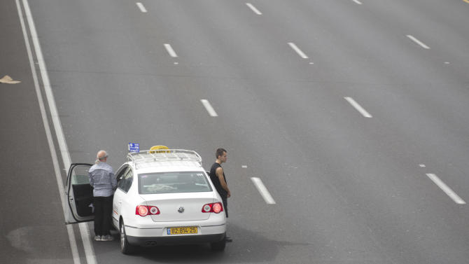 Israeli motorists stand still next to their cars on a freeway as a two-minute siren sounds in memory of victims of the Holocaust in Tel Aviv, Israel, Monday, April 8, 2013. Holocaust remembrance day is one of the most solemn on Israel's calendar with restaurants and places of entertainment shut down, and radio and TV programming focused on Holocaust documentaries and interviews with survivors. (AP Photo/Ariel Schalit))