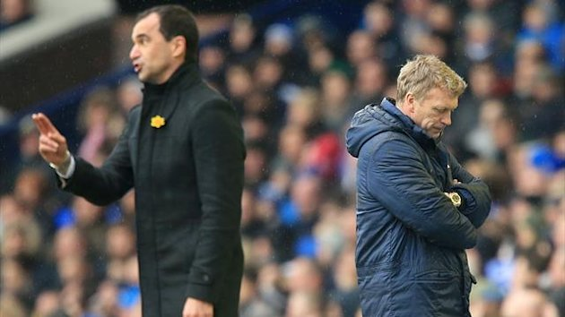 Everton manager David Moyes (right) walks away from the touchline as Wigan Athletic manager Roberto Martinez gies instructions to his players