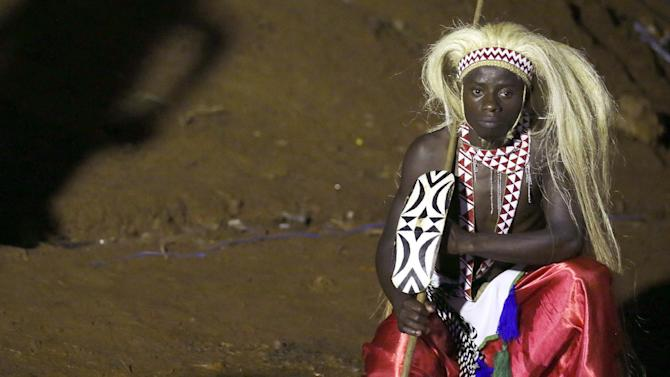 A man wears his traditional tribal clothing as he waits for the arrival of Pope Francis'  in Munyonyo in Kampala