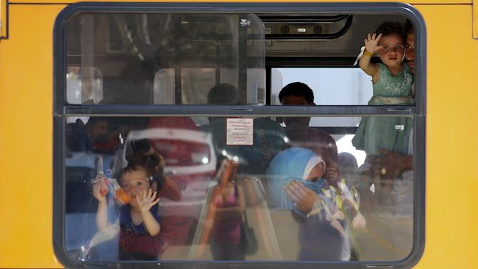 Migrants sit in a bus after they disembarked from the Irish Navy ship LE Niamh in the Sicilian harbour of Messina