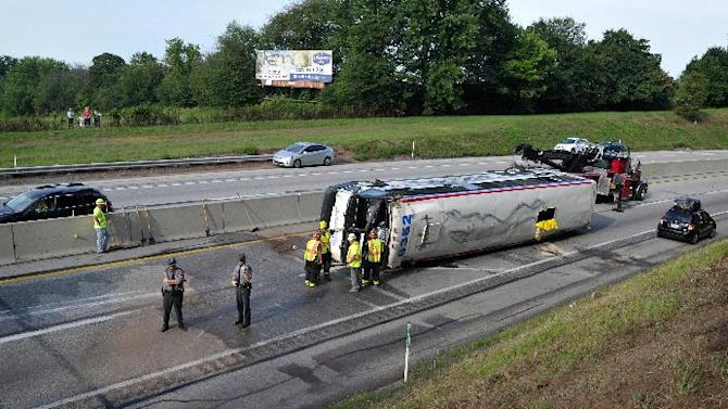 Emergency personnel work the scene where a Greyhound bus bound for St. Louis from New York City flipped on its side on the Pennsylvania Turnpike, briefly trapping a woman and injuring about two dozen people,  according to authorities, about one mile east of the Lancaster-Lebanon interchange, early Saturday, Aug. 13, 2011, near Manheim, Pa. (AP Photo/Lancaster Newspapers, Dan Marschka)