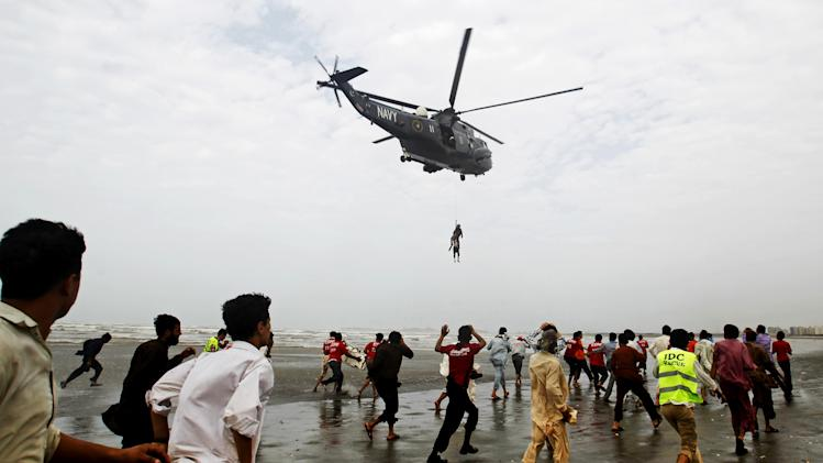 A Pakistan Navy helicopter evacuates a recovered body of a victim who drowned over Clifton beach in Karachi, Pakistan, Thursday, July 31, 2014. Scores of people drowned despite a ban on entering and bathing in the sea due to high tides, after thousands of people turned up on various beaches of Karachi to celebrate Muslims festive day of Eid. (AP Photo/Fareed Khan)