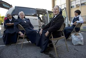 A group of nuns have a picnic near their van as they…
