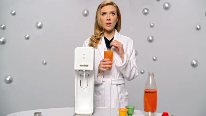 """This undated frame grab provided by SodaStream, shows the company's 2014 Super Bowl commercial. SodaStream's ad features """"Her"""" actress Scarlett Johansson promoting its at-home soda maker and will run in the fourth quarter. The ad, which promotes the product as a healthier and less wasteful way to make soda, made waves ahead of the game when the company said it would delete it's last line, """"Sorry, Coke and Pepsi,"""" at a request by Fox. (AP Photo/SodaStream)"""