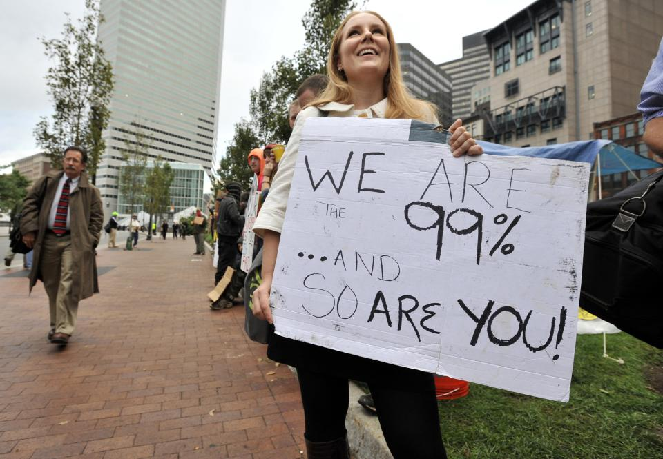 A woman who identified herself only as Jenna, and said she worked at an architecture firm in Boston's financial district, stops on her way to work to join demonstrators with Occupy Boston on Monday, Oct. 3, 2011. The group is part of a nationwide grassroots movement in support of the ongoing Wall Street protests in New York. (AP Photo/Josh Reynolds)