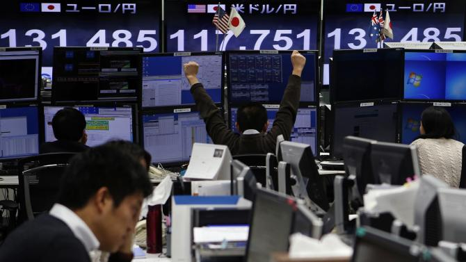 An employee of a foreign exchange trading company stretches in front of monitors in Tokyo