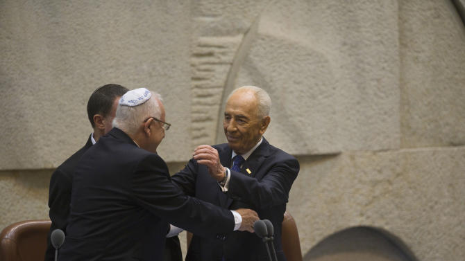 Outgoing Israeli President Shimon Peres (R) hugs Newly sworn-in President Reuven Rivlin during a ceremony at the Knesset, Israel's parliament, in Jerusalem, Thursday, July 24, 2014. Nobel Peace Prize laureate Shimon Peres ended his term as president of Israel on Thursday — a man who symbolizes hopes for peace capping a seven-decade public career amid the brutal reality of war. Peres handed the ceremonial but high-profile presidency over to Reuven Rivlin, a legislator from the hawkish Likud Party. (AP Photo/Ronen Zvulun, Pool)
