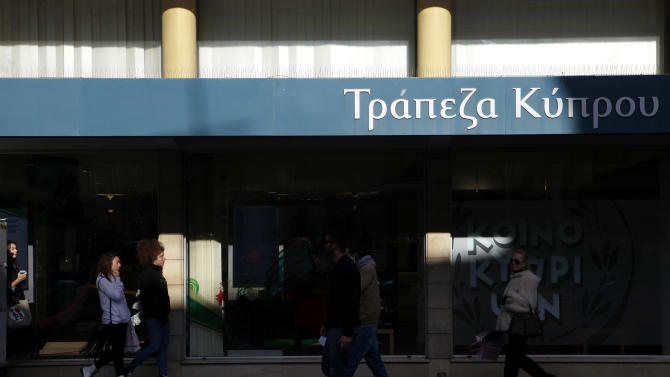 "Pedestrians pass a branch of ""Bank of Cyprus"" at a main street in Nicosia, Friday Dec. 21, 2012. The Cyprus government vowed to do what is needed to finalize a bailout agreement with international lenders after ratings agency Standard & Poor's downgraded Cyprus further into junk status amid concerns that the country could default on its debts. (AP Photo/Petros Karadjias)"