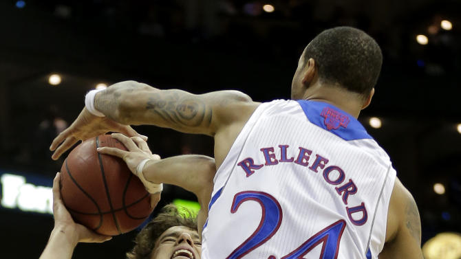 Kansas guard Travis Releford (24) blocks a shot by Texas Tech guard Dusty Hannahs (2) during the first half an NCAA college basketball game in the Big 12 men's tournament Thursday, March 14, 2013, in Kansas City, Mo. (AP Photo/Charlie Riedel)