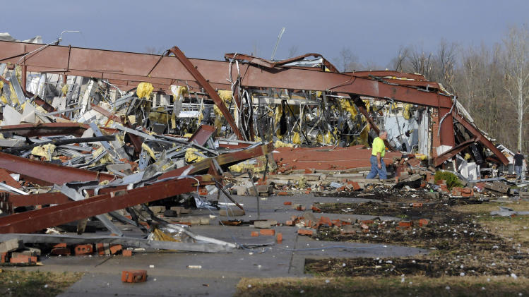 An employee of Henryville High School examines the remains of the building following severe storms Friday, March 2, 2012, in Henryville, Ind. Tornadoes ripped across several small southern Indiana towns on Friday, killing at least three people and leaving behind miles of flattened devastation along the border with Kentucky. (AP Photo/Timothy D. Easley)