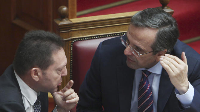 Greece's Prime Minister Antonis Samaras, right, speaks with Greece's Finance Minister Yannis Stournaras during a vote on a privatization bill at the Greek parliament in Athens, Wednesday, Oct. 31, 2012. Greek lawmakers are to vote Wednesday on a privatization bill that will be the first major test for the country's troubled governing coalition, while journalists have walked off the job at the start of rolling 24-hour strikes to protest austerity plans that will affect their healthcare funds. (AP Photo/Thanassis Stavrakis)