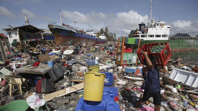 A Filipino boy carries bottled water amongst the damaged houses where a ship was washed ashore in Tacloban city, Leyte province, central Philippines on Sunday, Nov. 10, 2013. The city remains littered with debris from damaged homes as many complain of shortages of food and water and no electricity since Typhoon Haiyan slammed into their province. Haiyan, one of the most powerful storms on record, slammed into six central Philippine islands on Friday, leaving a wide swath of destruction and scores of people dead. (AP Photo/Aaron Favila)