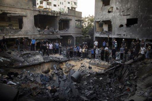 Palestinian men gather around a crater caused by an Israeli air strike on the Dallu family's home in Gaza City