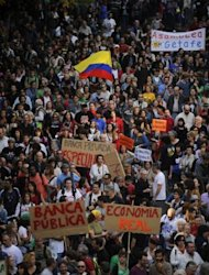 "<p>People hold placards and banners reading, ""Public bank. Real economy"" and ""Private bank. Speculation"" as they take part in a march against government's austerity reforms in Madrid.</p>"