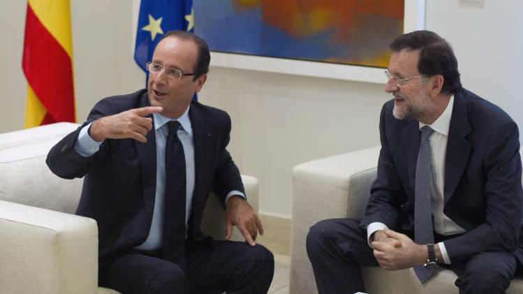 French President Francois Hollande, left gestures at the start of a meeting with Spain's Prime Minister Mariano Rajoy, right, at the Moncloa Palace in Madrid Thursday Aug. 30, 2012.  Hollande met Rajoy for talks on Spain's economic crisis and the future of the euro. (AP Photo/Paul White)