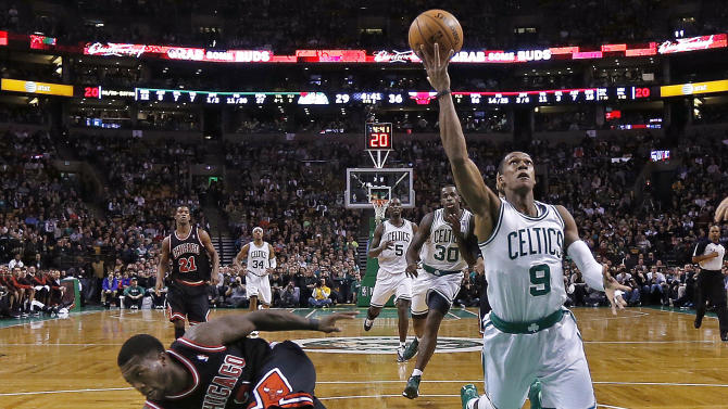 Boston Celtics guard Rajon Rondo (9) knocks Chicago Bulls guard Nate Robinson, left, out of the way as he drives to the basket during the first half of an NBA basketball game in Boston on Friday, Jan. 18, 2013. (AP Photo/Charles Krupa)