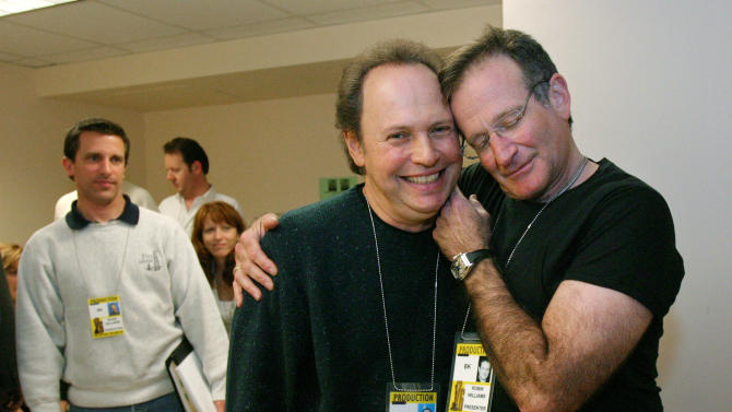 """FILE - This Feb. 28, 2004 file photo shows Oscar host Billy Crystal, center, and presenter Robin Williams, right, joking around after a writers' meeting for the 76th annual Academy Awards in Los Angeles. The producer of the Emmys says that Billy Crystal will pay tribute to Robin Williams during the awards ceremony. Executive producer Don Mischer said that Crystal will honor Williams as part of the traditional """"in memoriam"""" segment for industry members who died during the past year. Williams was found dead by suicide in his Northern California home Aug. 11. (AP Photo/Kevork Djansezian, File)"""