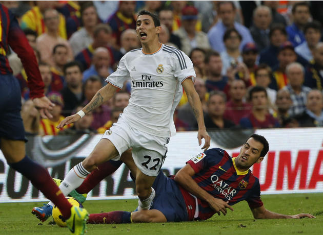 Barcelona's Sergio Busquets challenges for the ball with Real Madrid's Angel Di Maria from Argentina during a Spanish La Liga soccer match between Barcelona F.C. and Real Madrid at the Camp Nou stadiu