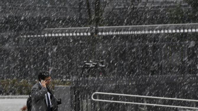 A man using a mobile phone walks on a street as snow falls in Tokyo