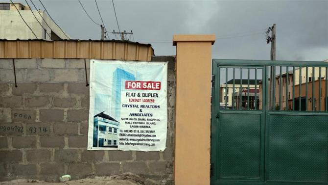 A sign advertising the sale of a house is pasted on a wall in the Victoria Island district in Nigeria's commercial capital Lagos